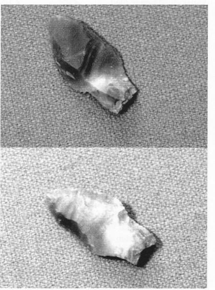 Figur 6. Flintredskapet ble funnet i hulvegen og klassifiseres som flekke med retusj. Redskapet er 7,0 Cm langt fra tange til Spiss, og 3,6 cm på det bredeste fra egg til egg. (Foto: T. Gansum).