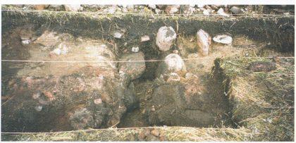Felt HII:4, 2001. Grøften K4/01 sett fra nord mot sør, der den forsvinner inn i profilen. I forgrunnen ses kanten av gropen K5/01 og åpningen mot grøften. (Foto: Eli Ulriksen.)
