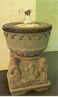 Døpefonten i Nøtterøy kirke. Den runde skålen er helt enkel og ganske nyhuggen. Det eldre, figursmykkete fotstykket er visstnok et gotlandsk arbeid fra ca. 1200.