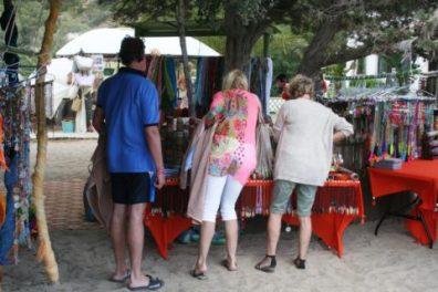 Tres turistas se interesan por los productos de uno de los puestos.