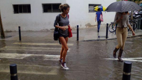 Una joven cruzando la calle en plena lluvia.