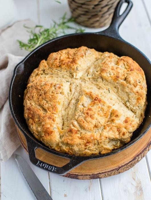 Rosemary cheddar Irish soda bread fully baked in a black cast-iron skillet.