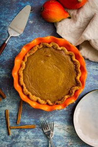 Overhead picture of bourbon molasses-spiked pumpkin pie, unsliced in an orange pie plate.