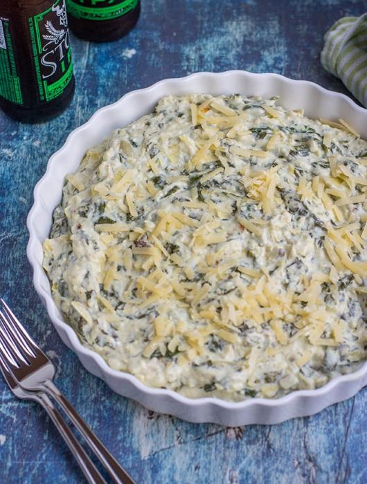 A round serving dish filled with creamy, cheesy spinach artichoke dip.