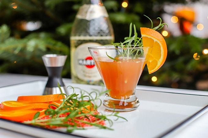 A short champagne flute filled with a light pink orange pomegranate Prosecco cocktail, garnished with rosemary and an orange slice.
