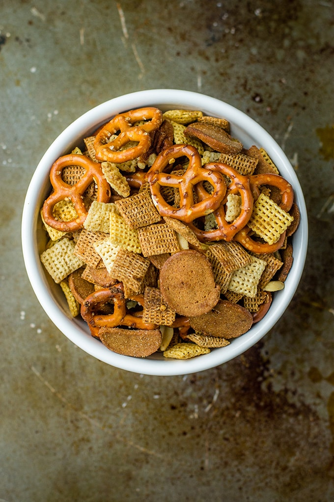 Flat-lay of a simple white bowl filled with rye chips Chex mix.
