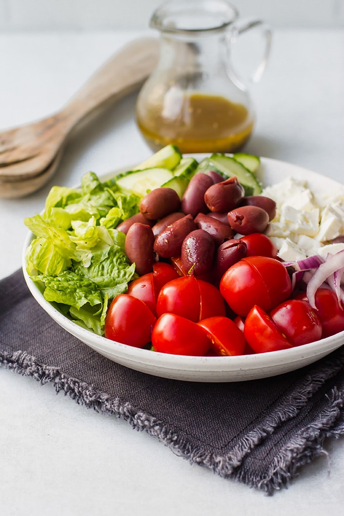 Photo of a simple Greek salad with romaine lettuce, cherry tomatoes, kalamata olives, cucumber, red onion, and feta cheese.