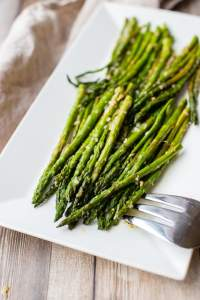 Roasted lemon pepper asparagus plated on a rectangular white tray.