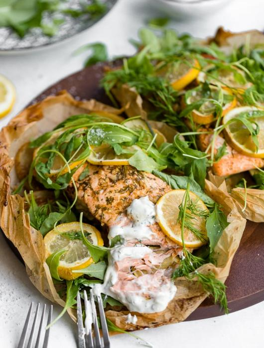Lemon salmon with potatoes and zucchini, served with fresh arugula and herbs and a dill yogurt sauce.