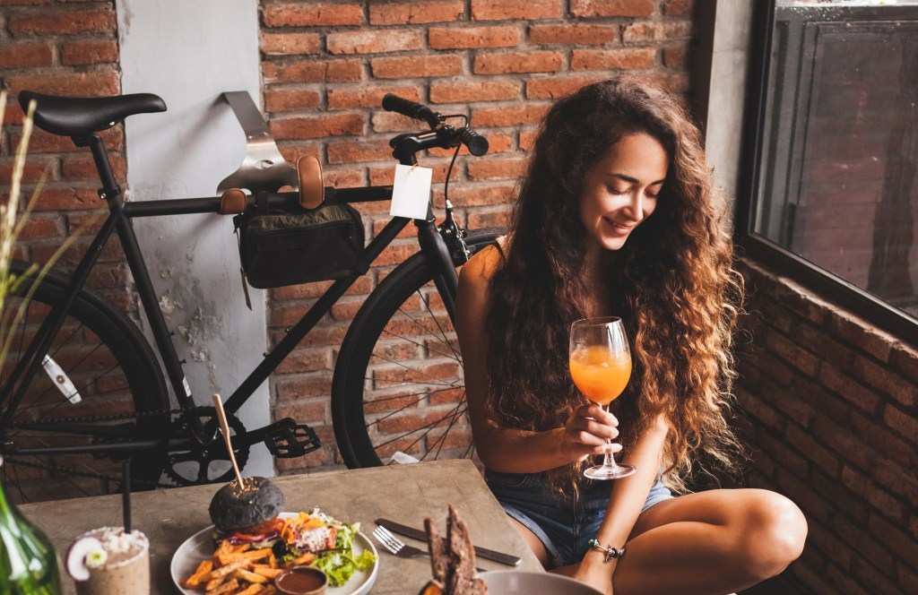 Millennial drinking kombucha in a cafe with her bike