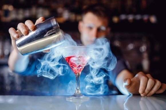 Bartender pouring high-end smoky cocktail