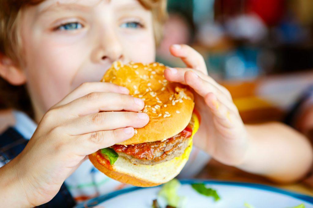 A child enjoys a large hamburger