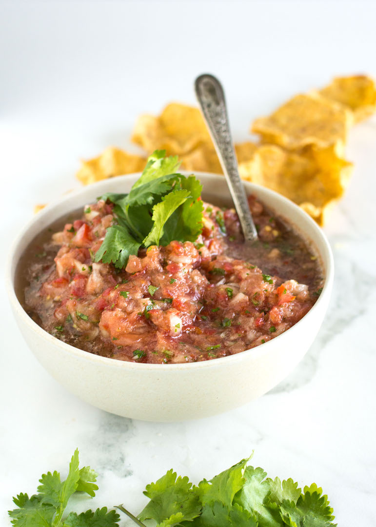 Easy Homemade Salsa | nourishedtheblog.com | A Homemade Salsa recipe made gluten free and vegan using cilantro, jalapeno, tomatoes, onion, garlic and lime juice. This super easy and insanely fresh salsa is made from scratch in about 10 minutes and pairs perfectly with guacamole and lightly salted corn chips for a tasty snack.
