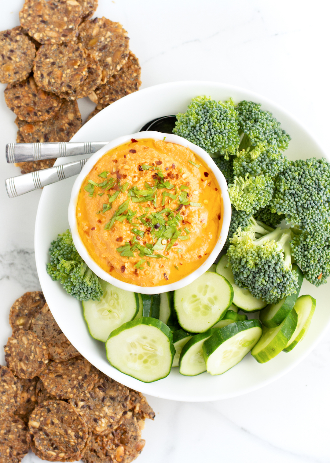 Homemade Roasted Red Pepper Hummus is the best healthy afternoon snack. Loaded with red peppers, chickpeas, tahini, lemon juice and garlic this clean eating recipe is delicious served with veggies and crackers.