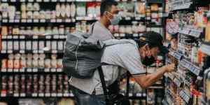 two men in a grocery store looking at items on the shelf
