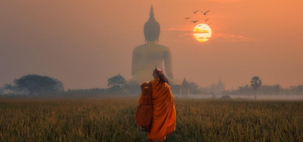 Mnich na tle posągu Buddy
