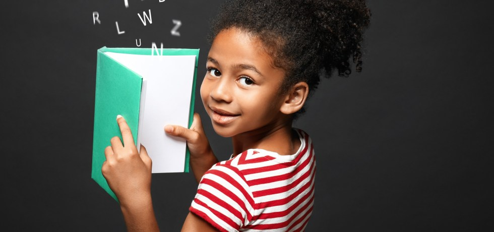 Afro-American girl with a book and letters of the alphabet