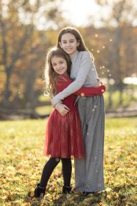 Sisters hugging at norther Virginia family photography session.