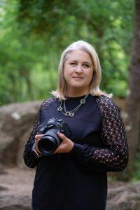 Rebecca of NOVA Portraits Headshot holding a camera