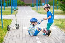 Helpful-kids-boy-pulling-up-rollerskating-brother-by-Pahis-500x-istock-min