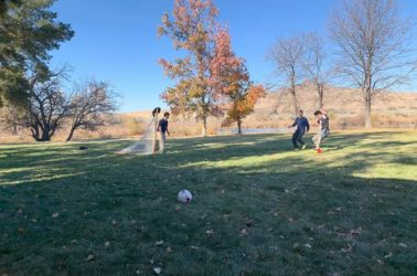 A group of students play soccer outside near Novitas Academy.