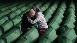 Bosnian Muslim women comfort each other, seen among coffins of Srebrenica victims displayed at Memorial center of Potocari near Srebrenica, 120 kms northeast of Sarajevo on Friday, July 9, 2010. The 775 bodies were excavated from mass-graves in Eastern Bosnia and were identified as Muslims killed by Bosnian-Serb forces in the Srebrenica area. Bosnian Serb troops massacred up to 8,000 Bosnian Muslim men after capturing Srebrenica on July 11, 1995, during the 1992-1995 war in Bosnia-Herzegovina. The 775 identified victims will be buried on July 11 in the Memorial Center Potocari. (AP Photo/Amel Emric)