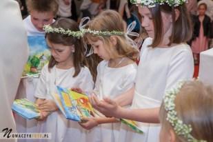 Sesja komunijna dziewczynki w kościele w otoczeniu innych dzieci