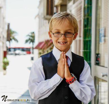 Sesja komunijna chłopca stojącego z uliczce z rękami złożonymi do modlitwy