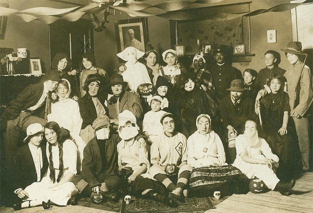 This 1908 Halloween party shows young women dressed as male-female couples. Its location is not indicated.