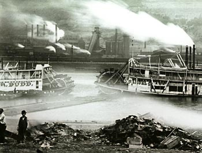Steamboats pass in the smoke-induced night. Sligo Iron Works on the South Side contributes to the effect. Workers on the nearside are not to be left out.  Did they just set fire to a pile of debris?