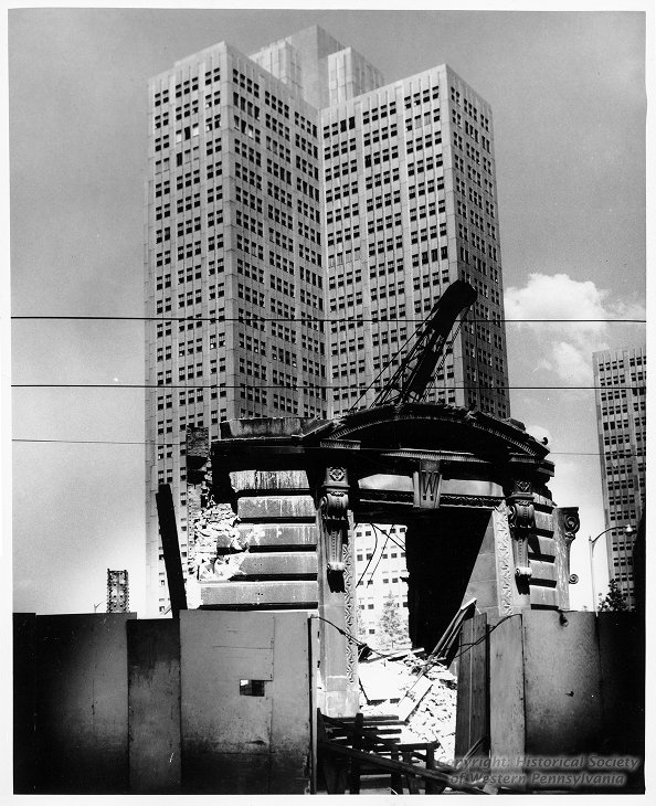 One of the gleaming metal buildings of Gateway Center looms behind the doorway of the Wabash Train Terminal during its demolition in 1954.