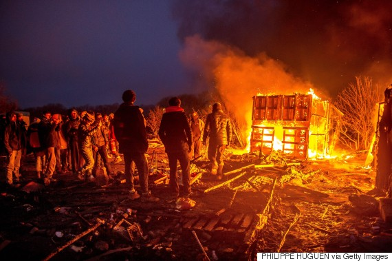 """Migrants stand next to a fire burning shacks, in the southern part of the so-called """"Jungle"""" migrant camp, as half of the camp is being dismantled, in the French northern port city of Calais, on March 1, 2016. In the northern French port city of Calais, tensions were high as officials for a second day razed part of the Jungle camp, which has become a magnet for people hoping to reach Britain. / AFP / PHILIPPE HUGUEN (Photo credit should read PHILIPPE HUGUEN/AFP/Getty Images)"""