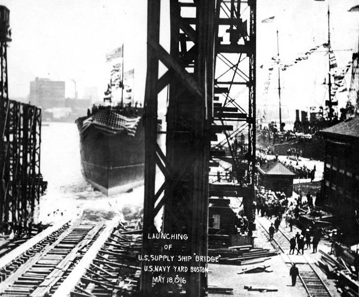 Photograph of a large supply ship sliding off the shipways into Boston Harbor.  Crowds are gathered on the pier to the right of the shipways, as both the supply ship and  USS Constitution to the right are dressed in flags.