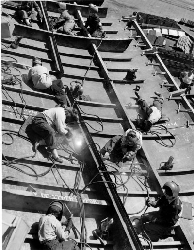 Black and white photograph of many women spread out and welding plates together to form a hull.