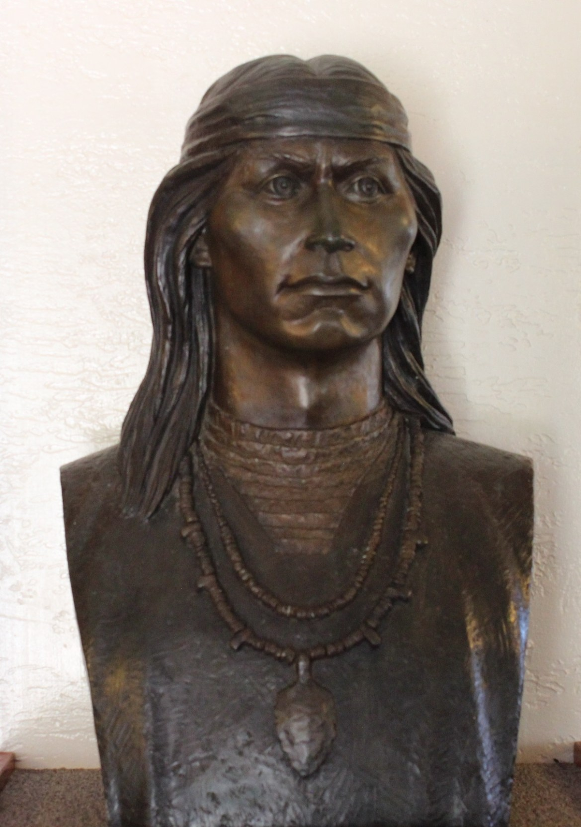 A statue bust of a man wearing a headband over his long hair, and two necklaces.