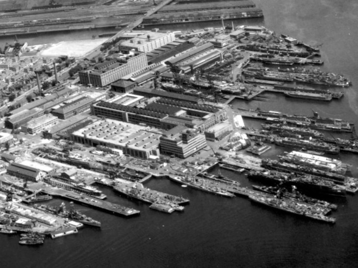 Photograph of roadways, piers, buildings, dry docks, and ships at a naval shipyard.