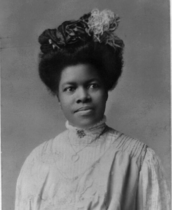 Black and white photo of a young Nannie Helen Burroughs wearing a dark hat.