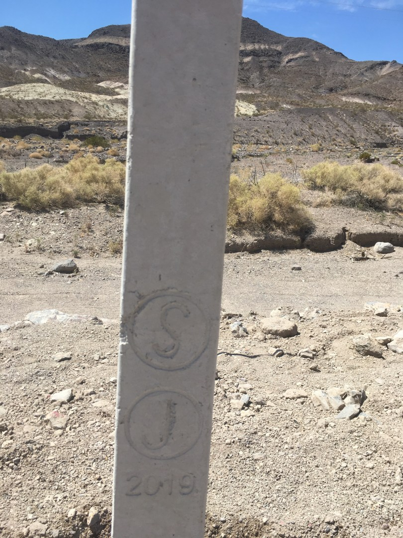 A close-up photo of a concrete fence post, stamped with a circle-S, circle-J, and 2019.