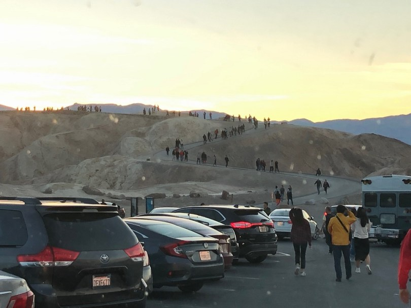 Photo shows a crowded parking lot in the foreground and visitors walking the trail to Zabriskie Point at sunset in the background.