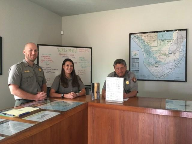 3 rangers staffing a visitor center desk