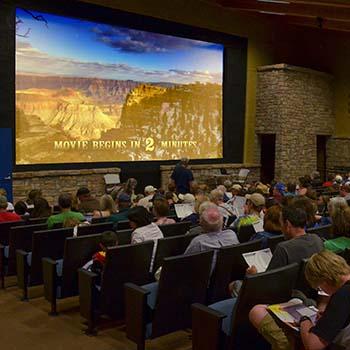 """""""Film 2 Dakikada Başlar"""" yazan ekrana bakan tiyatro sıralarında oturan insanlar."""