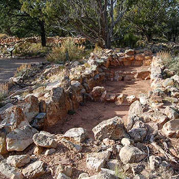 Kısmi kaya duvarları, tarih öncesi bir pueblo'nun birkaç odasını özetlemektedir.
