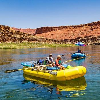 can yeleği giyen iki kişi, sakin nehir sularında sarı bir şişme sal kürek çekiyor.  ikinci bir mavi sal onları takip ediyor.
