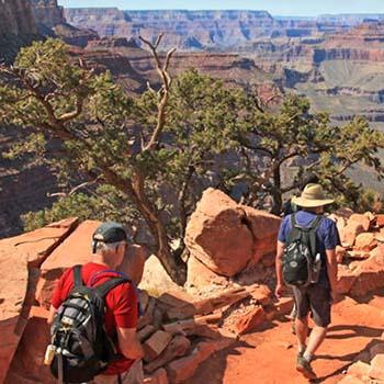 Yaz kıyafetleri giyen iki yürüyüşçü, geniş bir kanyona asfaltsız bir patikadan iniyor.