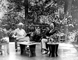 Herbert & Lou Henry Hoover seated on porch