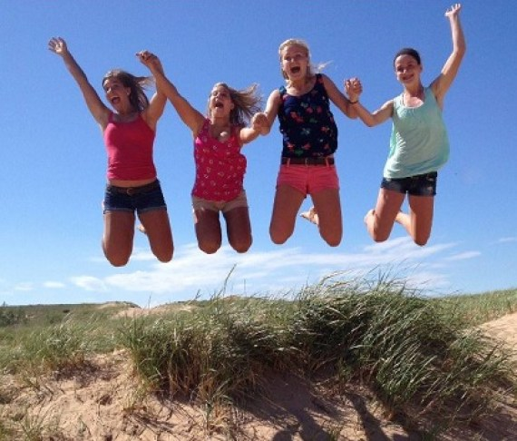 Four women jumping up on a sand dune