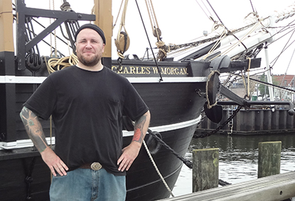 A man standing next to the bow of a vessel called the Charles W. Morgan.