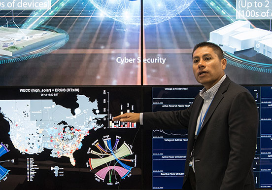 NREL Associate Laboratory Director for Energy Systems Integration Juan Torres points to map displaying renewable energy generation data across the United States.