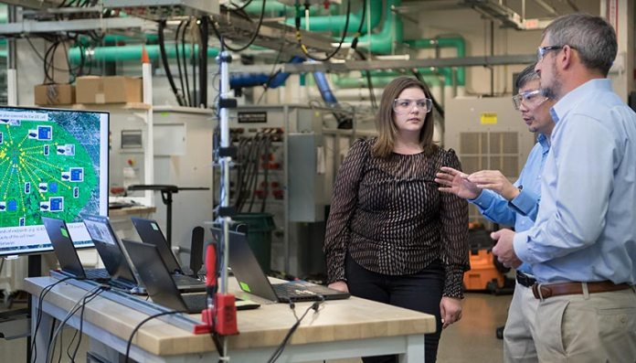 NREL researchers work on the advanced distribution management test bed in NREL's Energy Systems Integration Facility.