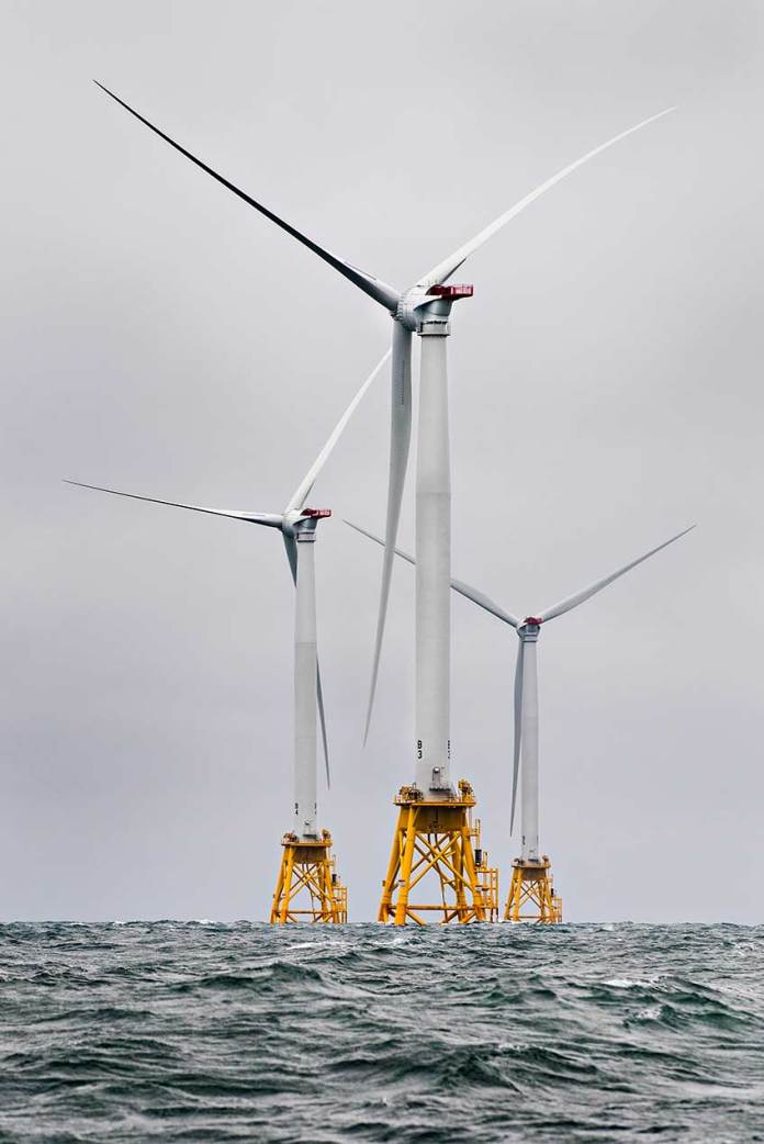 A photograph of three offshore wind turbines in the ocean.